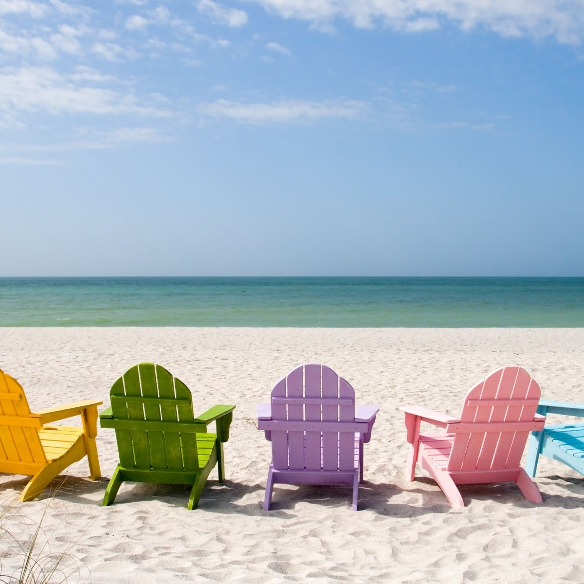 Ultimate Summer Bucket List - Pastel chairs in positioned in front of the water