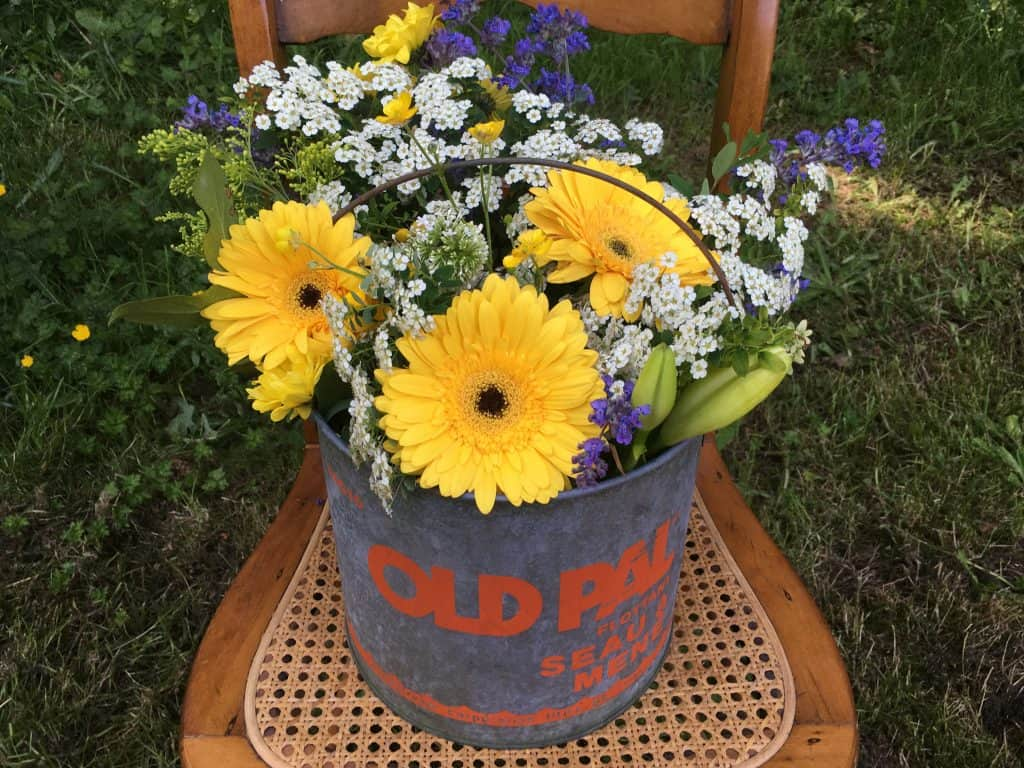 I love putting a flower pot in an old fishing bucket and place it on an unused chair.