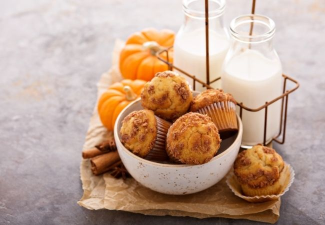 Bowl of Cinnamon muffins, two containers of milk and mini pumpkins