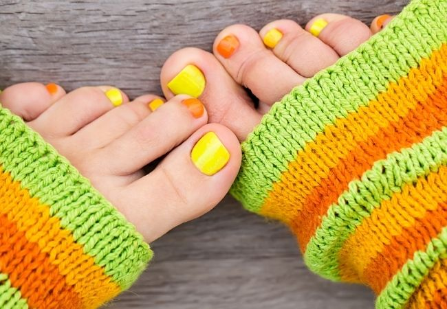 Picture of toe nails painted with orange and yellow nails with leg warmers
