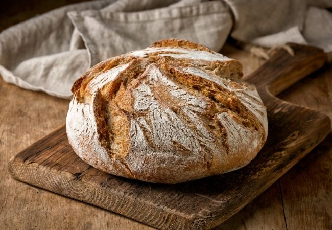 Homemade Loaf of Bread on a rustic cutting board
