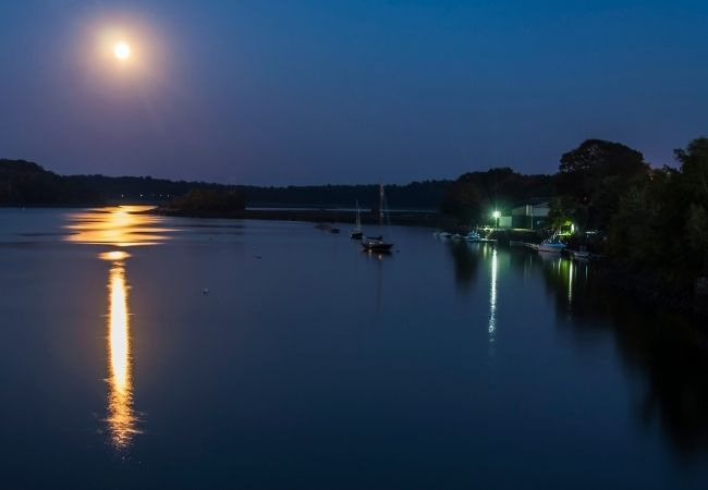 Moonlight over water and fishing boats