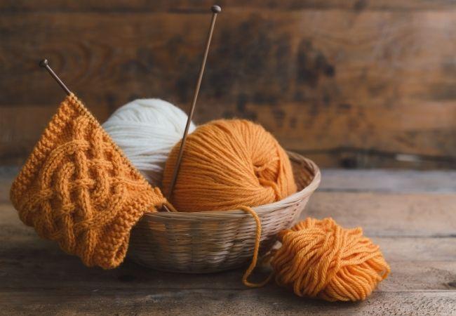 Bowl of yarn and knitting needles