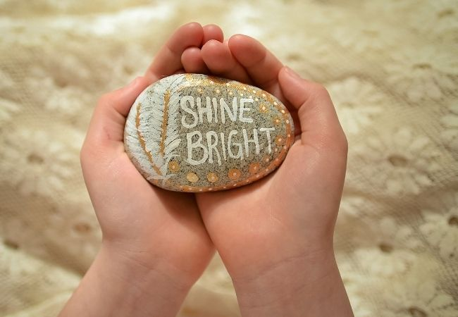 """Rock painted with words """"Shine Bright"""" and a feather"""