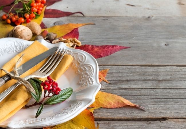 Plate, knife, and fork on table with fall foliage
