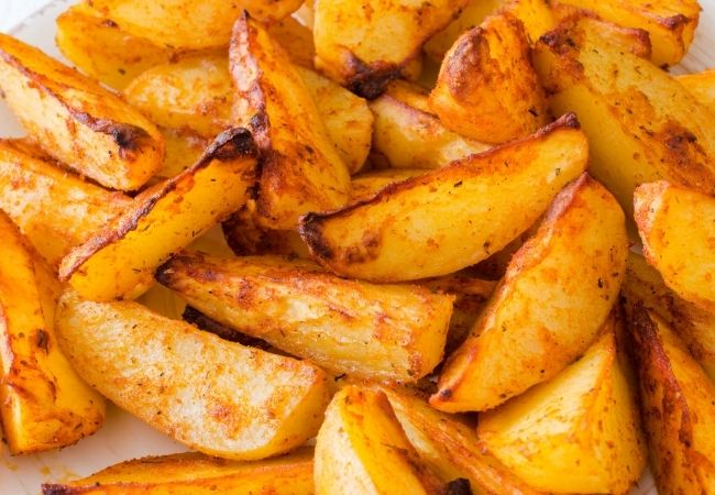 Roasted Buffalo Potato Wedges on parchment paper
