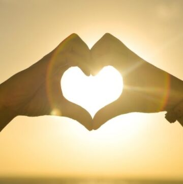 Two hands in the sky in front of full sun making a heart shape - Kindness Quotes to Inspire a Better World Heading photo