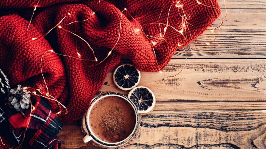 31 Day Hygge Christmas Photo Challenge - Pile of Blankets with mug of hot chocolate with fairy lights