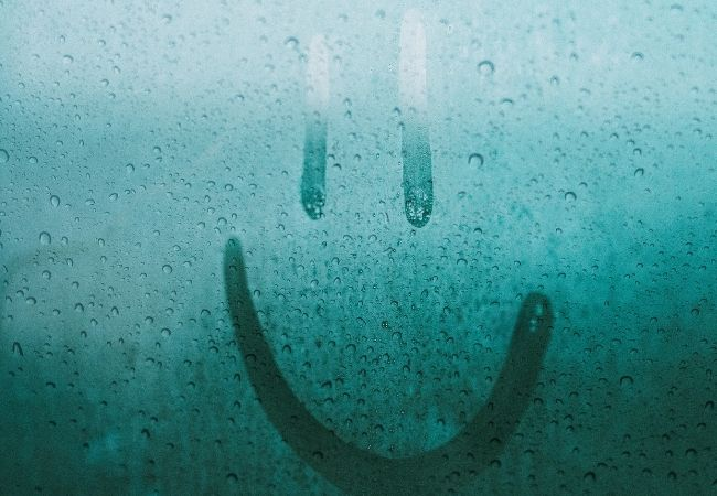 Smiley face drawn in the condensation in a window