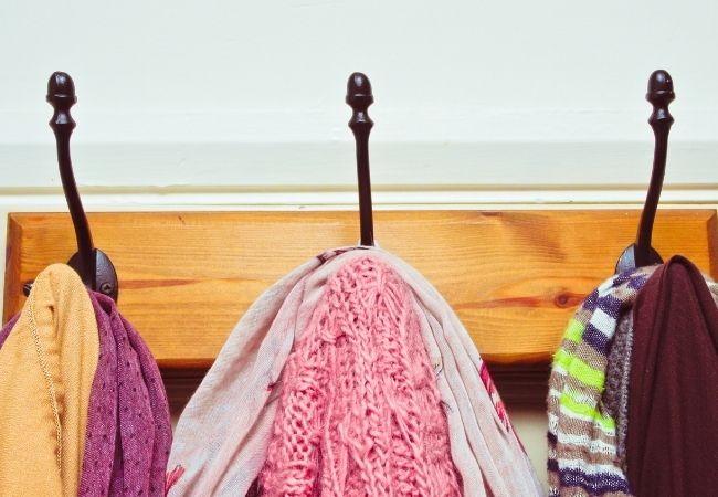 Wooden hook rack with clothing hanging from the hooks.