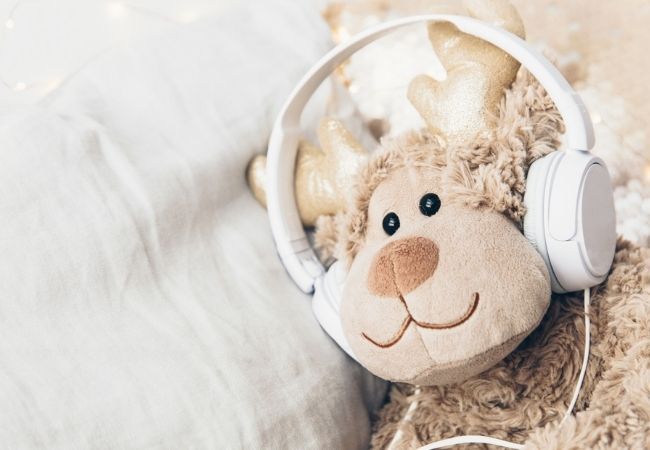Stuffed animal lying in bed with a set of headphones on