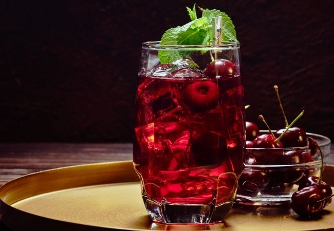 Clear glass on a tray with tart cherry juice, ice, and mint leaves. Small bowl of fresh cherries is besides it.
