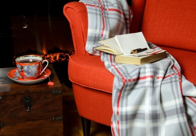 Rust wingback chair in front of a fire with book and cup of tea