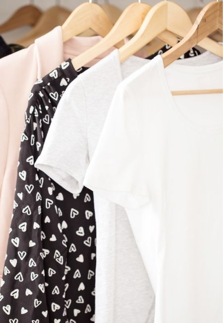 Clothes Closet with two white shirts, one black one and one pink