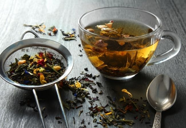 Herbs and dried flowers in a tea strainer and a cup of tea in a clear glass mug