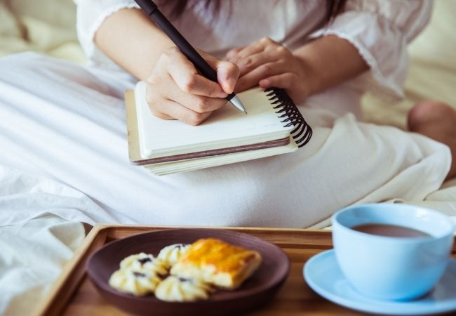 Writing in a notebook with a breakfast tray nearby