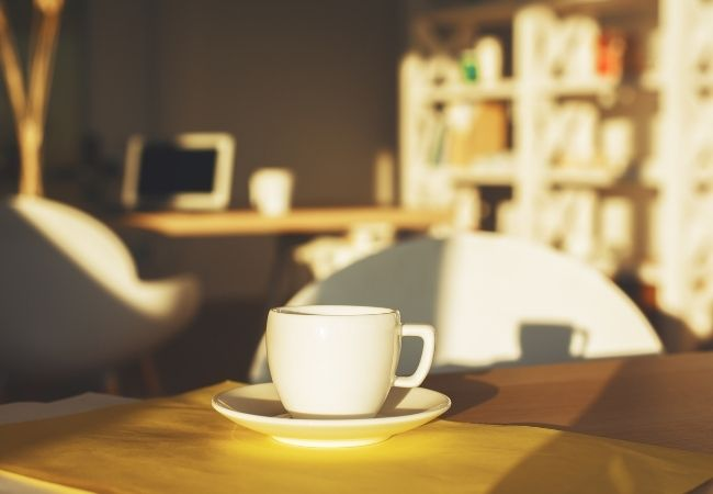 Kitchen table with morning sunlight and coffee cup with bookcase in the background