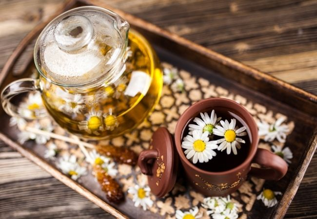 Rustic tray with pot with chamomile flowers floating on top of a mug