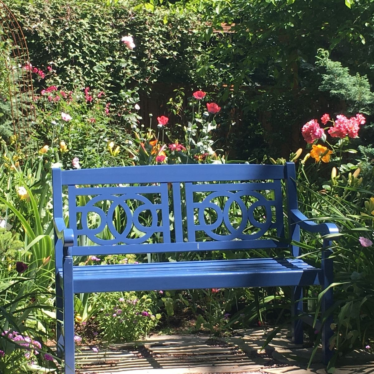 Hygge Garden Ideas - Blue bench in the middle of flowers