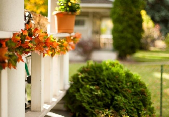Front porch railing decorated with fall leaf garland