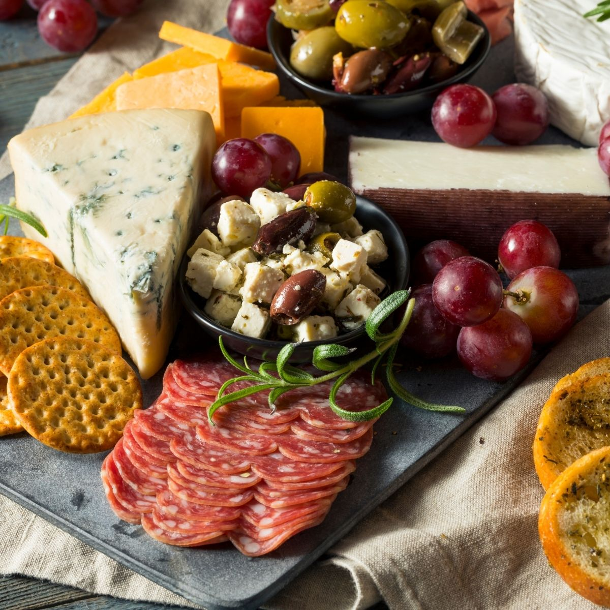 Easy Charcuterie Board Ideas - Slate Platter with olives cheese, crackers, salami,