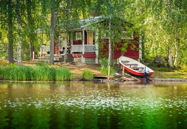 Red cottage by a lake with a small boat