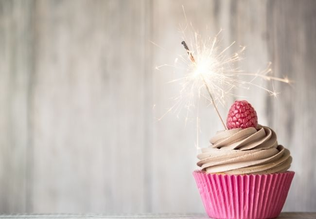 Cupcake with pink wrapper and chocolate frosting. Raspberry on top with a sparkler.