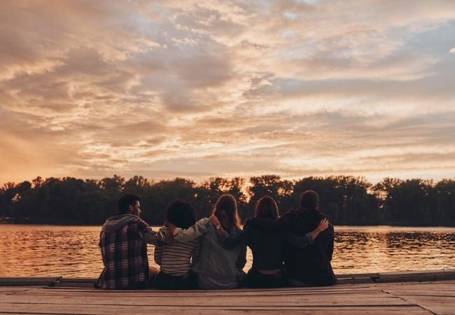 Five people with their backs to the camera sitting on a dock at sunset