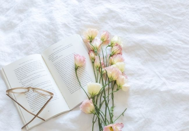 Open book with reading glasses and fresh flowers