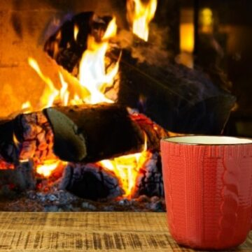 Close-up of a fireplace and an orange mug on a coffee table