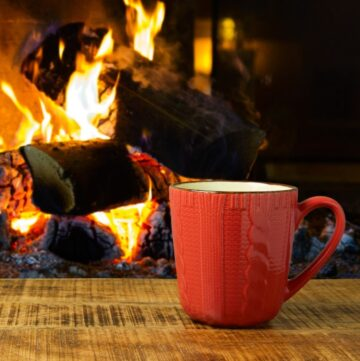 Hygge Quotes to Change Your Life - Orange Mug in front of a fireplace