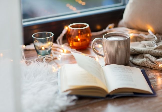 Open book next tow a window with fairy lights and coffee