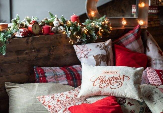 Close-up rustic bed with Christmas pillows and garland and lights