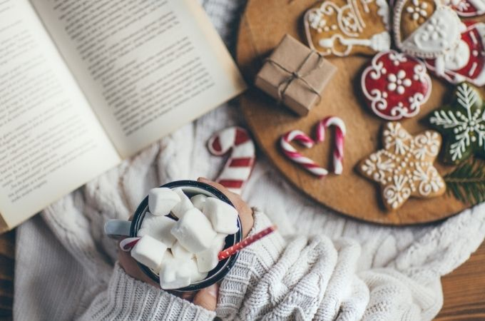 Close up of person's lap with book, Christmas cookies, and hot chocolate with marshmallows