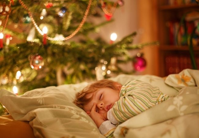 Child sleeping under the Christmas tree