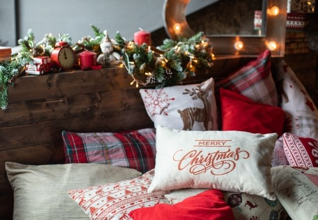 Bed with Christmas garland on headboard and Christmas pillows