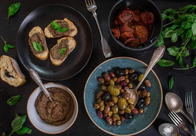 Black Olive Tapenade in a bowl and on crostini, dried marinated tomatoes, and a bowl of olives