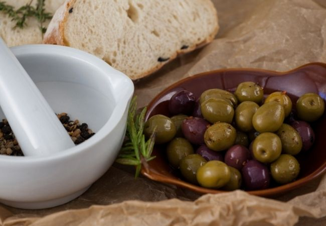 Slice of rustic white bread, bowl of green and black olives, and pestle and mortar with peppercorns