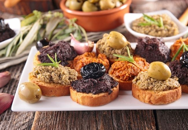 Crostini with black olive tapenade, green olive tapenade, and sun-dried tomato tapenade