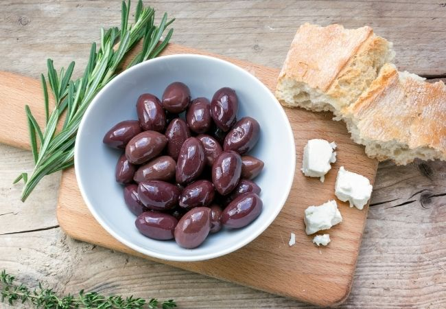 Bowl of Kalamata olives on cutting board with bread and fresh rosemary