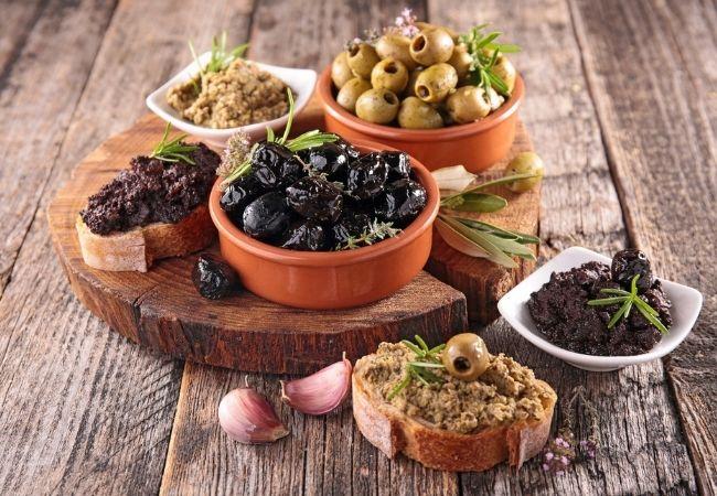 Olive Tapenade and Olive Bruschetta on a rustic cutting board