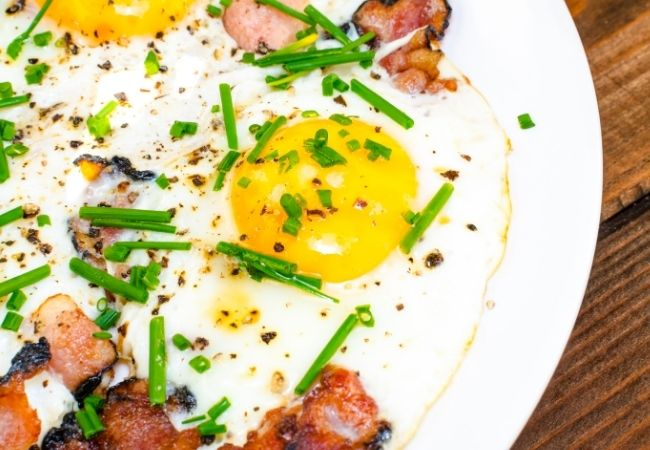 Over easy eggs and bacon topped with minced chives and pepper