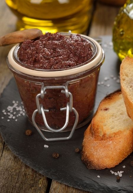 Close-up clear glass jar with olive tapenade and crostini