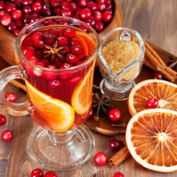 Easy Hot Cranberry Tea Recipe in clear glass mug with fresh cranberries and orange slices in the mug
