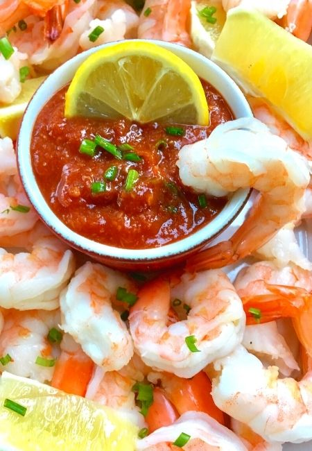 Close-up of cocktail sauce surrounded by shrimp with lemon and shrimp in the sauce.