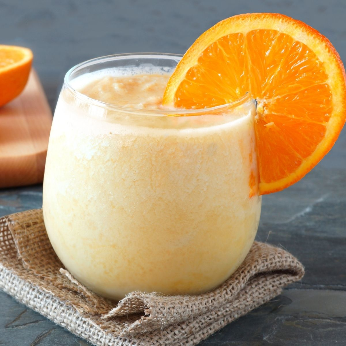 Orange Dreamsicle Smoothie Recipe in a clear glass with an orange slice on the rim