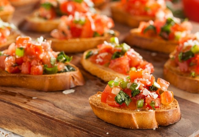 Themed Family Dinner Ideas - Appetizers - Slices of bruschetta on a wooden board