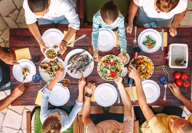 Themed Family Dinner Ideas - Overhead view of a family table with seven family members digging into food