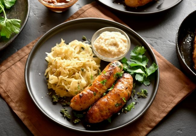 Themed Family Dinner Ideas - Around the World - a black plate with horserasdish sauce in a small bowl, sauerkraut, and sausages with a sprinkling of fresh chopped parsley