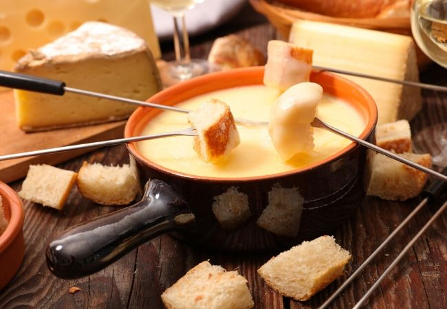 Themed Family Dinner Ideas - Fondue Night - Fondue pot with cheese fondue with fondue forks with bread resting on top. Wedges of cheese are in the background.